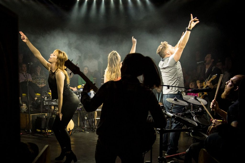 Three performers dance with hands in the air on stage, in the round. A female bassist is silhouetted in the foreground.