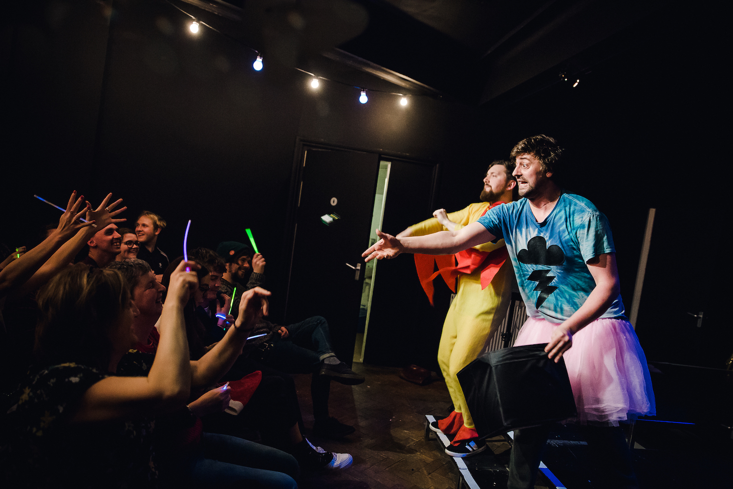 Two men in fancy dress stand on stage and point at a cheering audience