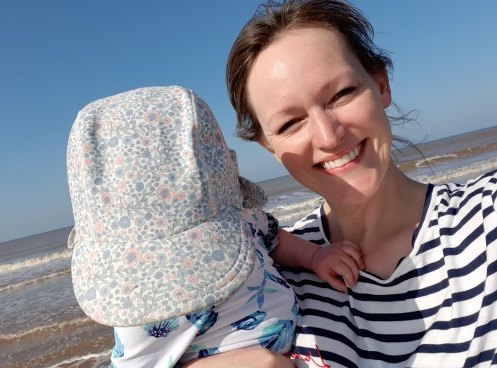 Lindsey Alvis, in a stripey top, holds her daughter on a bright day at the seaside.