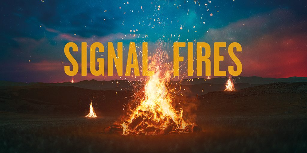 A small bonfire in the middle of a field at night. Text overlay: Signal Fires