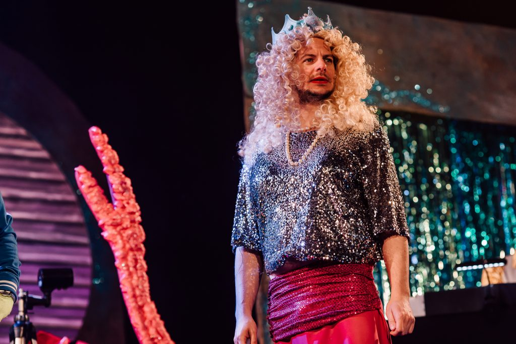 Marc Graham as Hull panto dame Pattie Breadcake, in a sparkly top and pink dress, with blonde wig and crown.