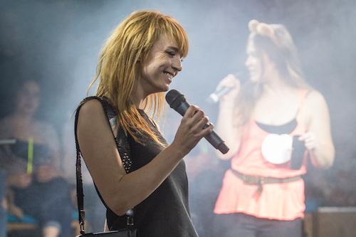 A woman on a night out smiles brightly while holding a microphone.