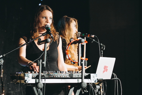 Two young women in black dresses play electronic instruments on stage