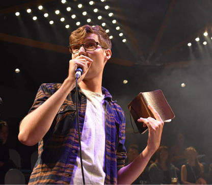 A man in white t-shirt and plaid shirt reads from a notebook into a mic