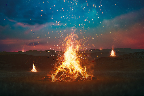 Bonfires burn across a nighttime landscape