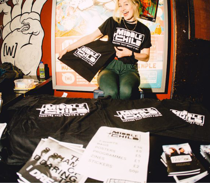 A young woman sits at a merch stall showing a black tote bag with Middle Child logo