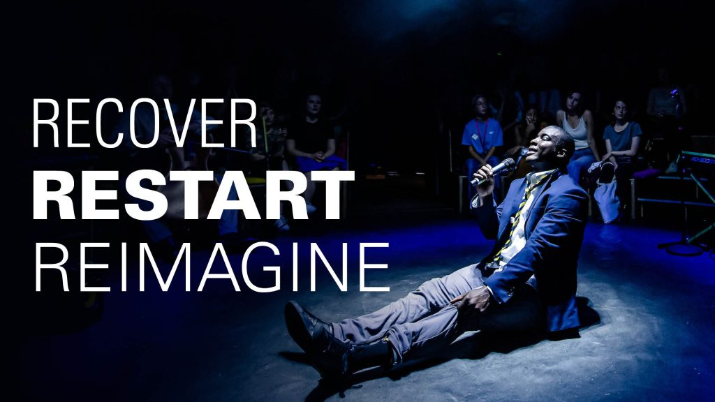 """An actor sits on the floor holding a mic. Text says """"Recover Restart Reimagine"""""""