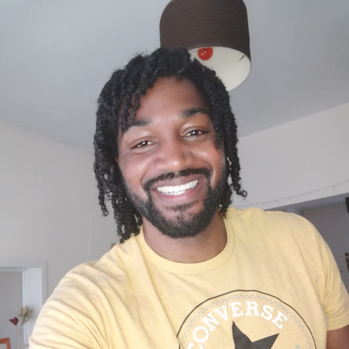 Headshot of a smiling Black man in a yellow t-shirt
