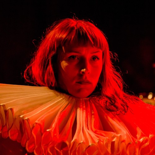 A white woman in a large ruff bathed in orange-red light