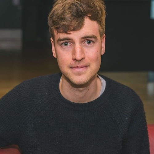Portrait of a young white man with light brown hair, wearing a navy blue jumper