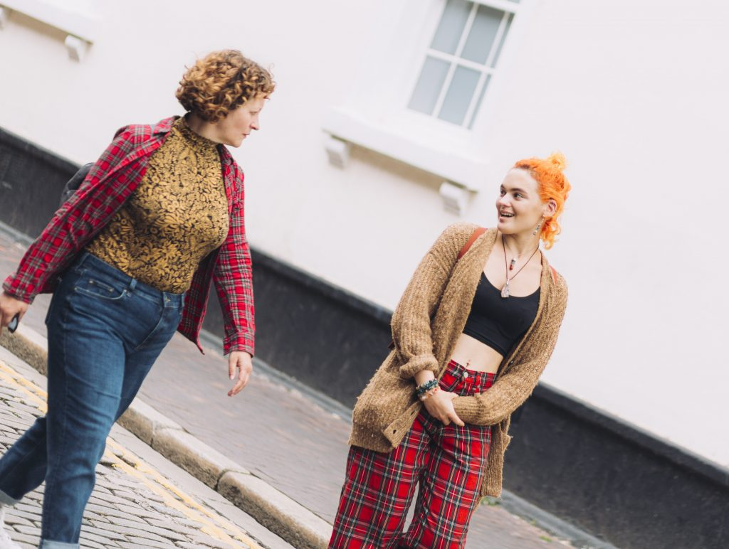 Two women walk and chat