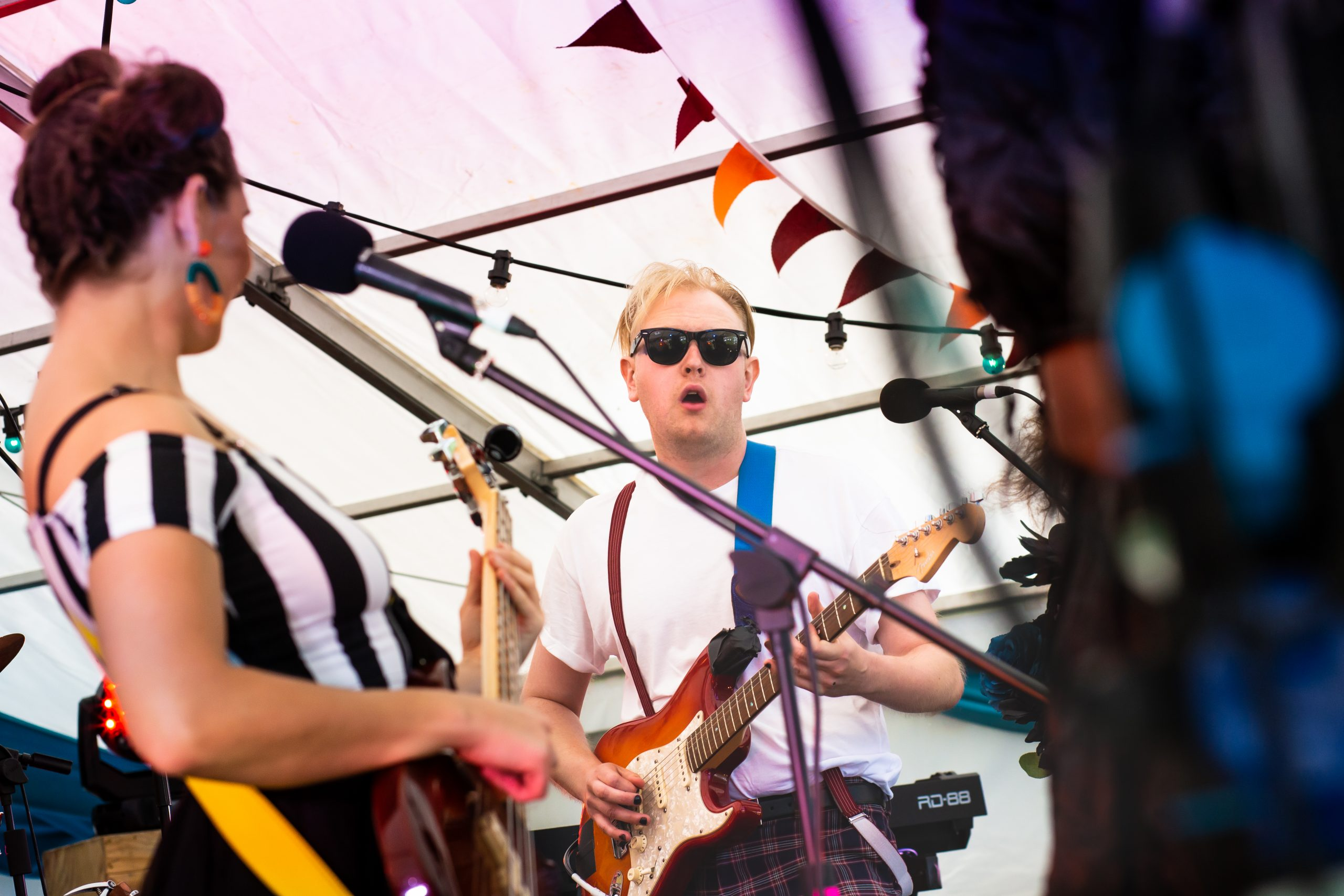 A band play guitars on stage beneath bunting