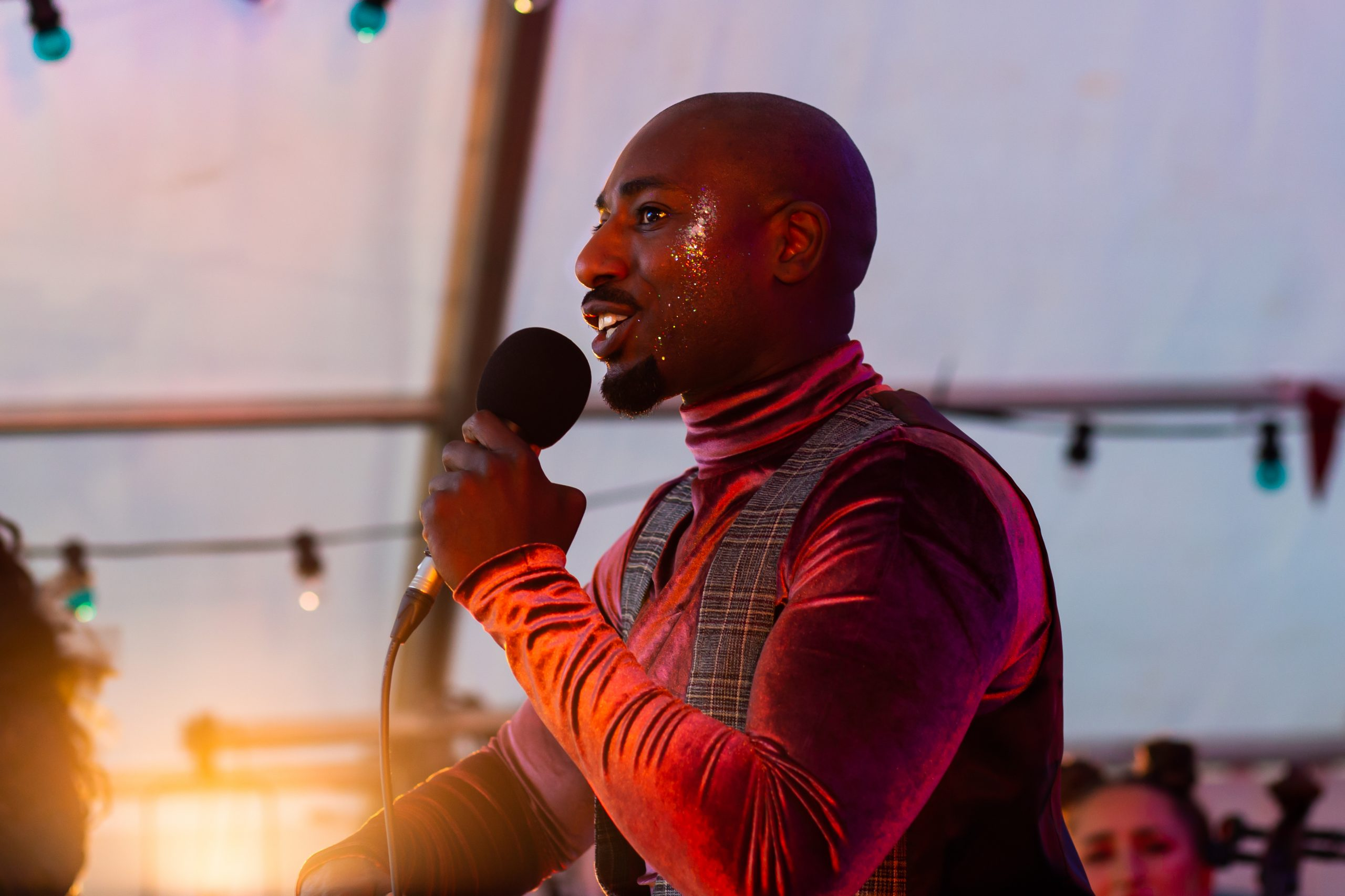 A Black man in velvet turtleneck and waistcoat sings into a microphone