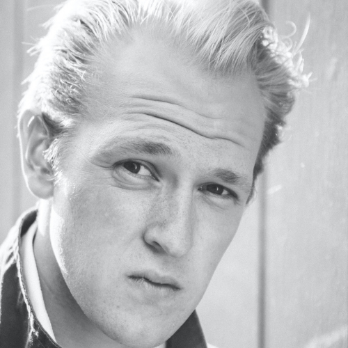 Black and white headshot of a white man with blonde hair combed back