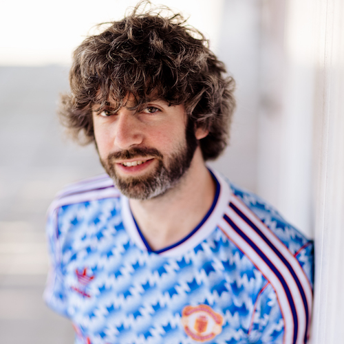A white man with dark curly hair and beard, wearing a blue Manchester United football shirt