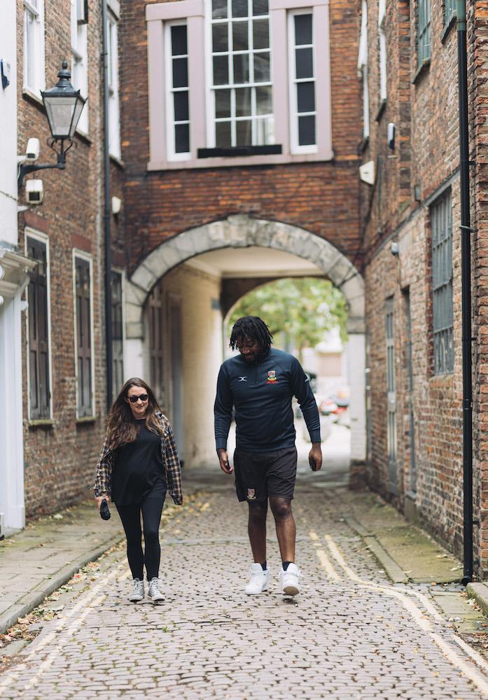 A short white woman and tall Black man walk down a cobbled Hull street