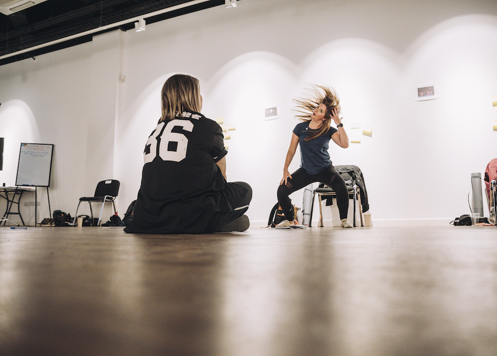 A woman sits cross legged, watching another woman dance