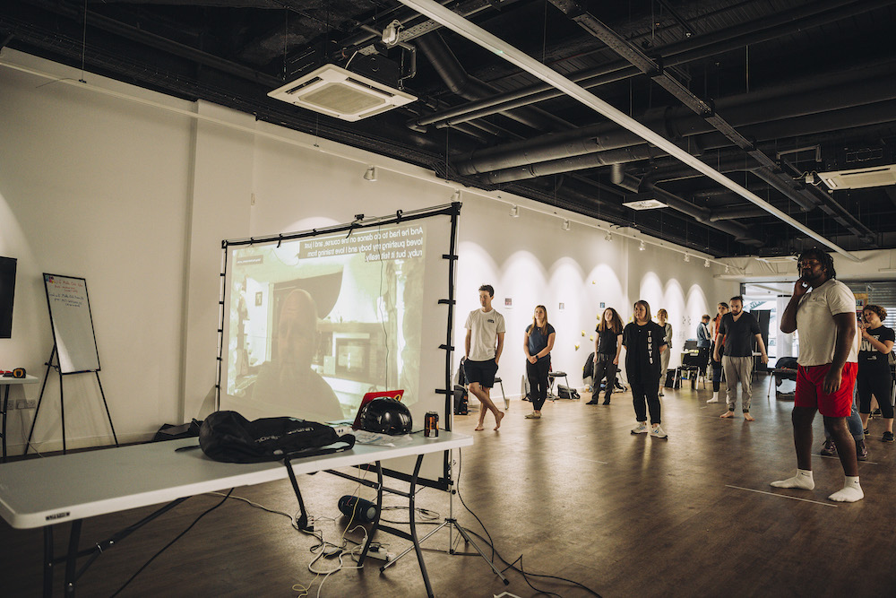 A group of performers stand and watch somebody speak via a projector screen