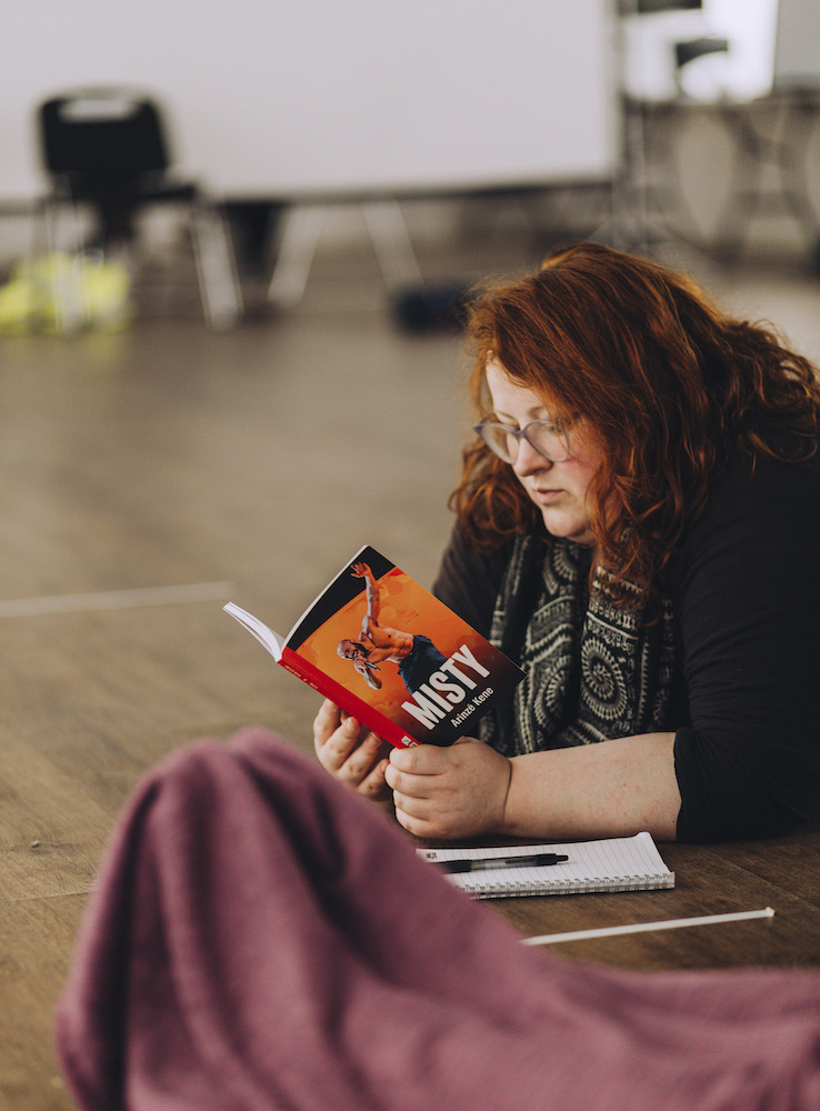 A white woman with ginger hair and glasses lies on the floor reading a playscript