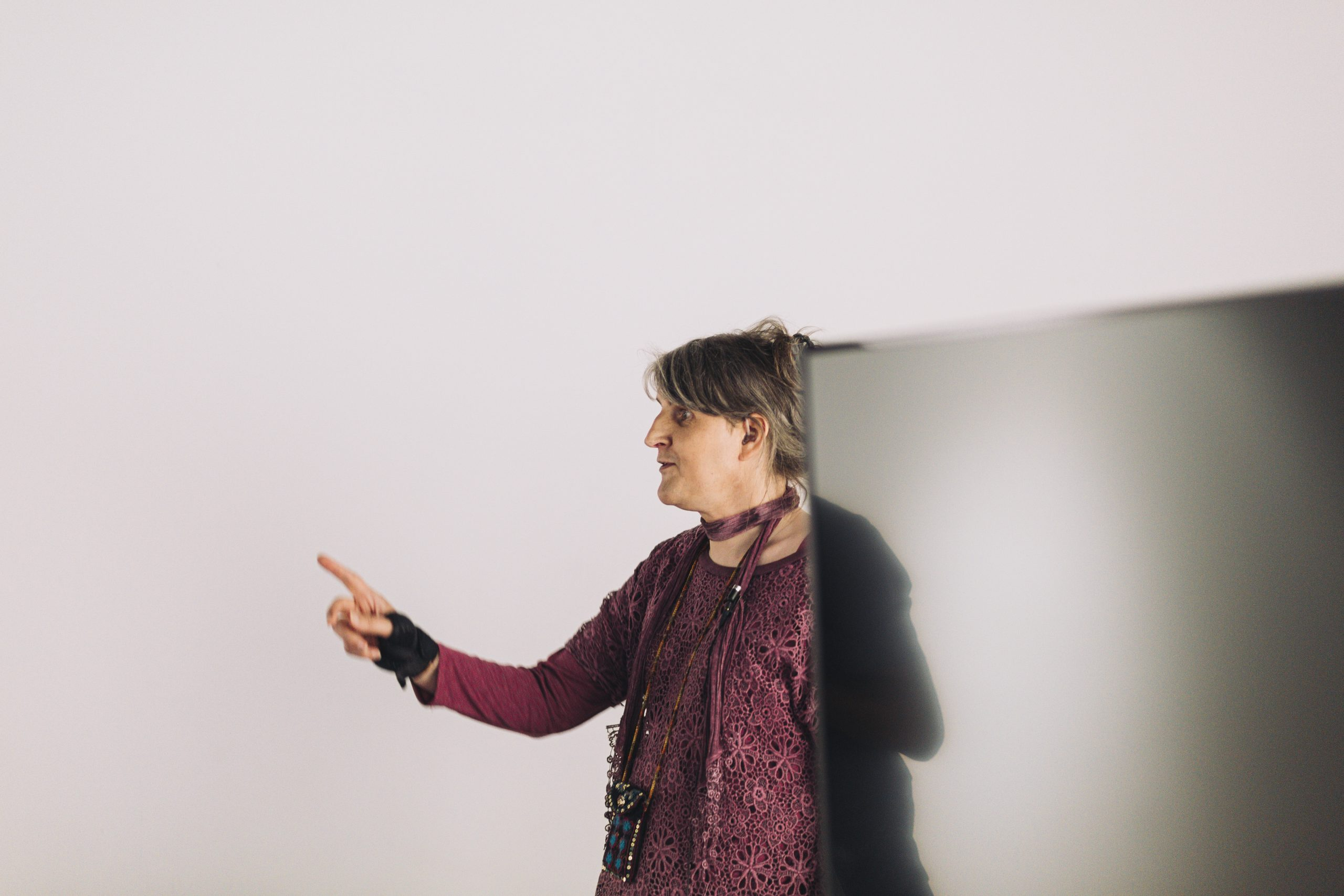 Michelle stands pointing off camera, standing behind a screen during our Recover, Restart and Reimagine project