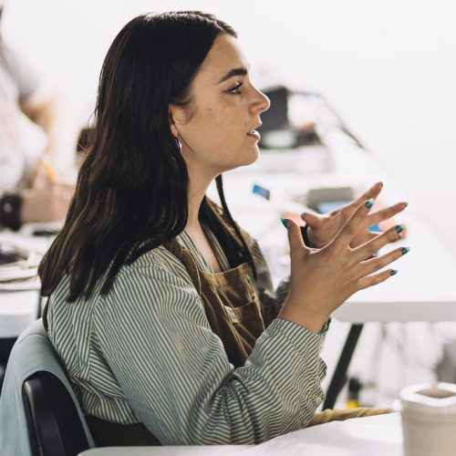 A white woman in brown dungarees with long dark hair gestures with her hands