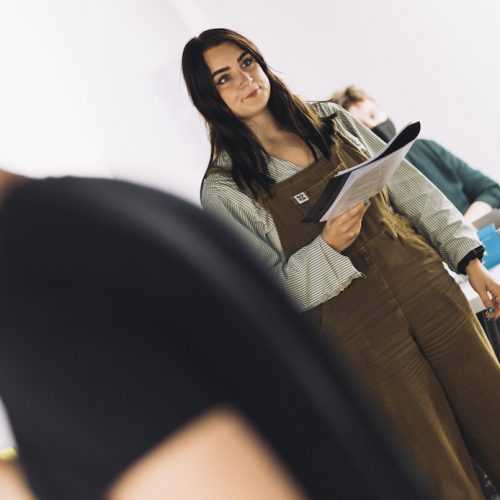 A white woman in brown dungarees stands holding a script