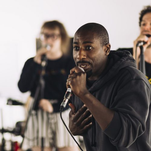 A Black man in a black hoodie performs into a microphone during rehearsals