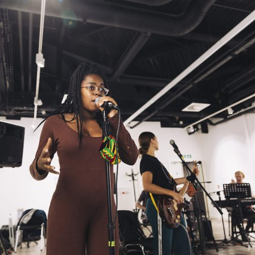 A Black woman in brown bodysuit speaks into a microphone during rehearsals